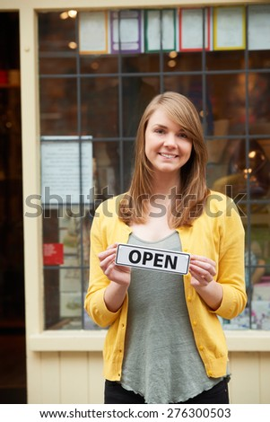 Portrait Of Owner Holding Open Sign Outside Gift Shop - stock photo