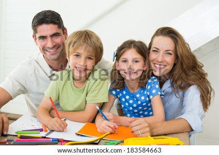 Portrait of parents with children drawing at home - stock photo