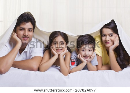Portrait of parents with children lying under bed cover - stock photo