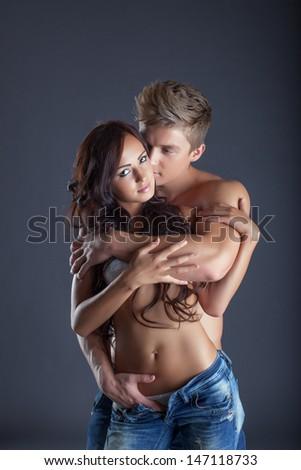 Portrait of passionate lovers posing in studio - stock photo