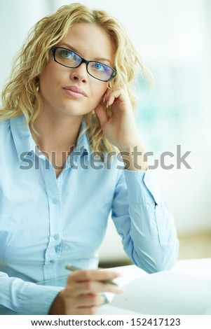 Portrait of pensive businesswoman in eyeglasses planning work - stock photo