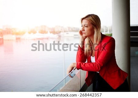Portrait of pensive businesswoman looking out of an office balcony with beautiful seaport view on background, unhappy successful woman standing in exterior,blonde woman looking out of her window sadly - stock photo