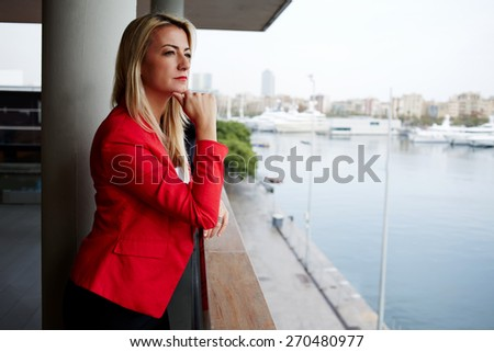 Portrait of pensive businesswoman looking out of an office balcony with beautiful seaport view on background, unhappy successful woman standing in exterior,blonde woman looking into the distance sadly - stock photo