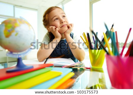 Portrait of pensive girl drawing with colorful pencils - stock photo