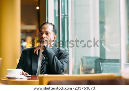 Portrait of pensive Indian businessman in the cafe - stock photo