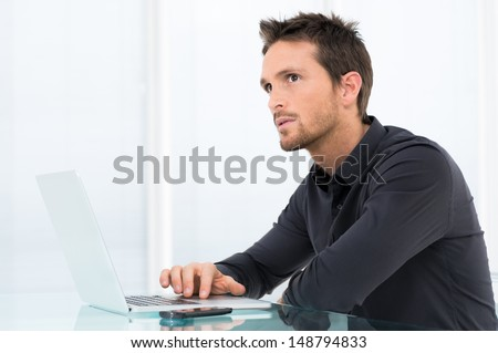Portrait Of Pensive Man Working On Laptop - stock photo