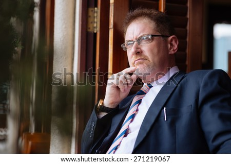 Portrait of pensive middle-aged businessman looking away - stock photo