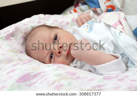 Portrait of pensive newborn baby on the bed at home - stock photo
