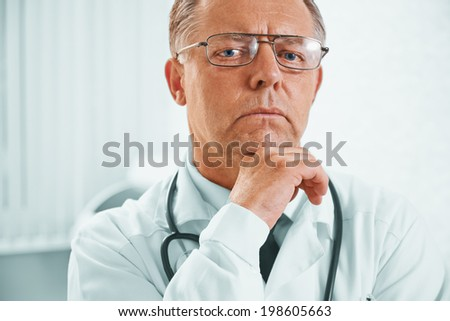 Portrait of pensive senior male doctor in hospital - stock photo
