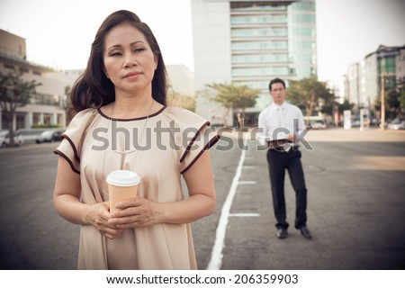 Portrait of pensive woman with a coffee cup and her male colleague in the background - stock photo