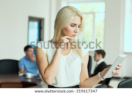 Portrait of pensive young business woman with a tablet computer at the office at a business meeting. - stock photo