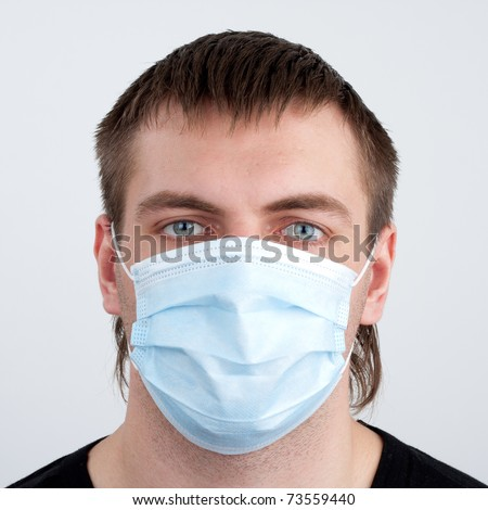 Portrait of pensive young man in medical mask - stock photo