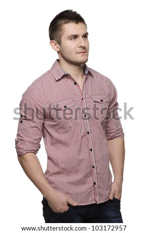 Portrait of pensive young man standing with his hands in pockets looking sideways, isolated on white background - stock photo