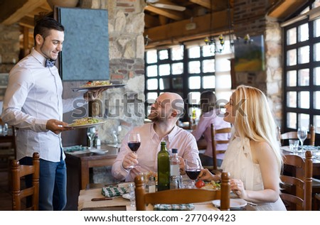 Portrait of people having dinner and respectful waiter - stock photo