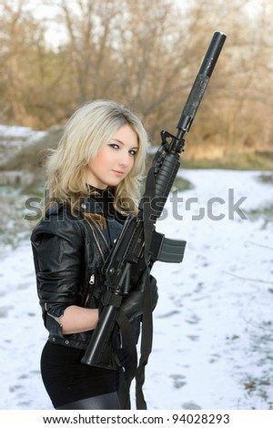 Portrait of perfect young blonde with a gun outdoors - stock photo