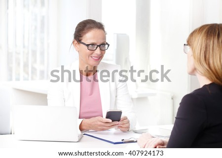 Portrait of personal banking advisor businesswoman consulting with her client about investment while sitting at office in front of computer. - stock photo
