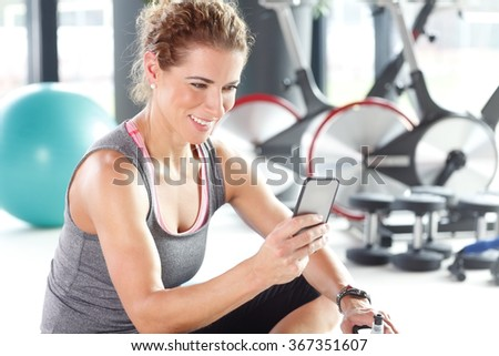 Portrait of personal trainer woman sitting at gym after fitness workout and checking sport app in her smartphone. - stock photo
