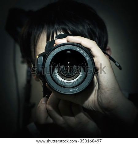 Portrait of photographer with camera in hand closeup - stock photo