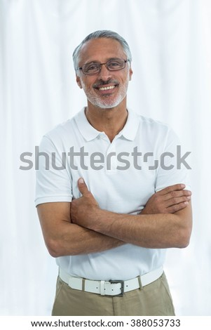 Portrait of physiotherapist smiling and standing with arms crossed at home - stock photo