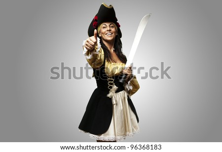 portrait of pirate woman holding a sword and gesturing ok against a grey background - stock photo