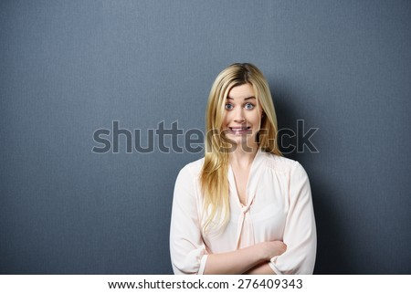 Portrait of Playful Blond Woman Wearing Light Colored Blouse with Arms Crossed with Exaggerated Smile and Copy Space to the Side - stock photo