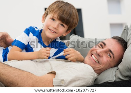Portrait Of Playful Father And Son Enjoying On Couch - stock photo