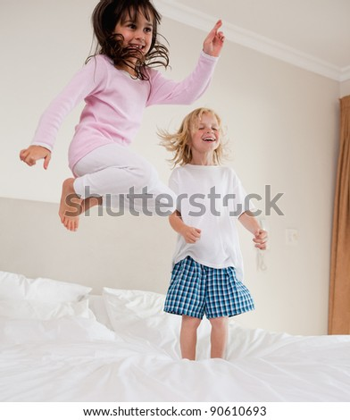 Portrait of playful siblings jumping on a bed - stock photo