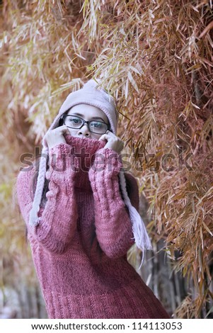 Portrait of playful woman with winter sweater on autumn day - stock photo