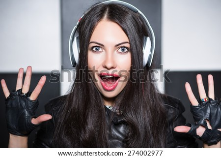 Portrait of playful young woman yelling in headphones - stock photo