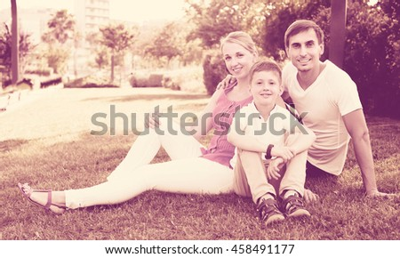 Portrait of positive family with boy in school age sitting on green lawn in park - stock photo
