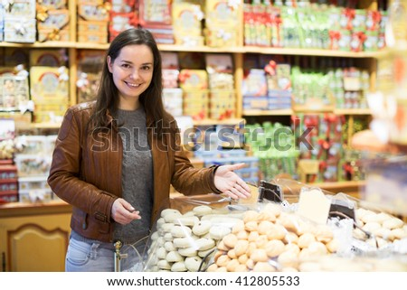 Portrait of positive female customer buying sweets in confectionery - stock photo
