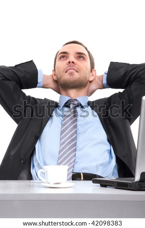 Portrait of positive man relaxing at workplace with hands behind head - stock photo