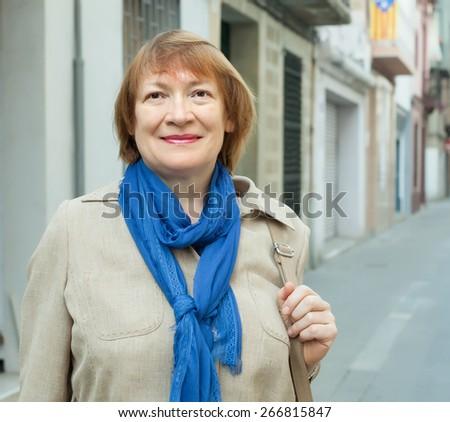 portrait of positive senior woman at town street - stock photo