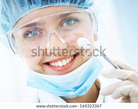 Portrait of positive smiling dentist with dental mirror - stock photo