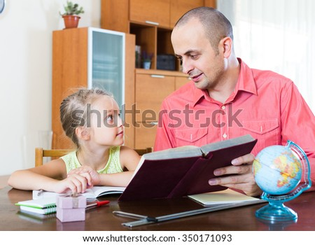 Portrait of positive spanish dad helping schoolgirl to study at home - stock photo