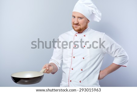 Portrait of positive young male chef in white uniform. Head-cook holding pan and looking at camera. Standing against grey background - stock photo