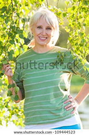 Portrait of positivity senior woman in summer park - stock photo