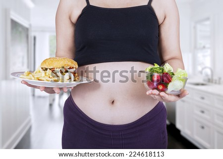 Portrait of pregnant mother showing healthy and unhealthy food - stock photo
