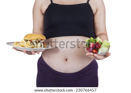 Portrait of pregnant woman holding a plate of junk food and a bowl of healthy food - stock photo