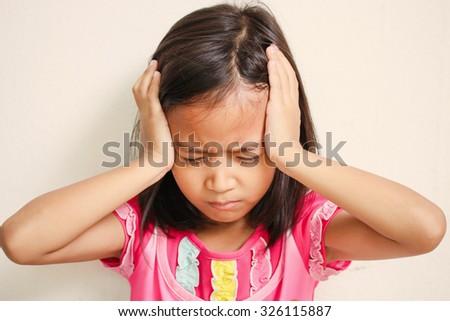 Portrait of preschooler girl having a headache - stock photo