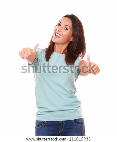 Portrait of pretty adult lady on blue t-shirt with thumb up smiling at you while standing on isolated white background - stock photo