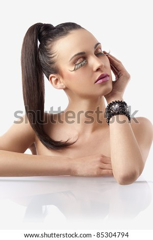 portrait of pretty and sensual brunette with hair pony  tail and creative make up with long eyelashes posing - stock photo