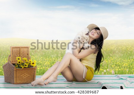 Portrait of pretty Asian girl hugging a maltese dog while sitting on the mat at the meadow - stock photo