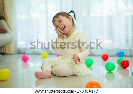 Portrait of pretty asian little girl talking on mobile phone - stock photo