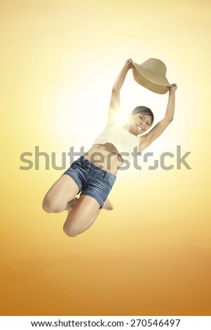 Portrait of pretty asian woman holding a hat and jump under beautiful dusk - stock photo