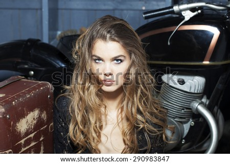 Portrait of pretty attractive young woman in black lace blouse sitting near old fashioned motorcycle with aged brown suitcase in garage on grey wooden wall background, horizontal picture - stock photo