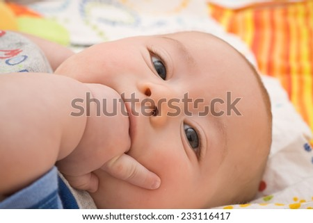 portrait of pretty baby biting his fist - stock photo