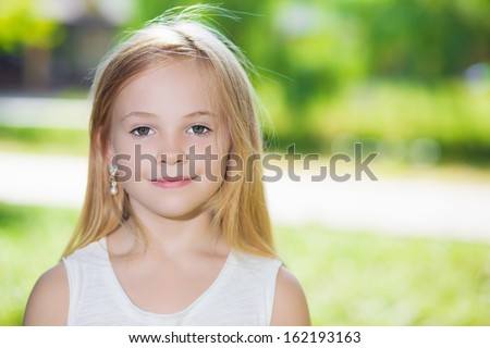 Portrait of pretty blond girl posing outdoors - stock photo