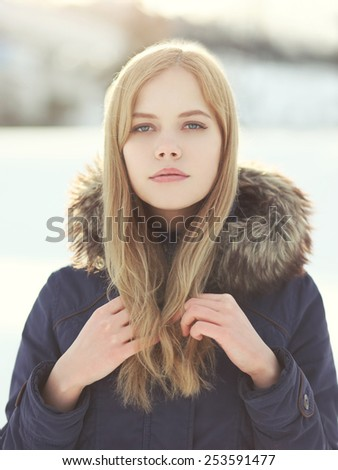 Portrait of pretty blonde girl outdoors in sunny winter day - stock photo