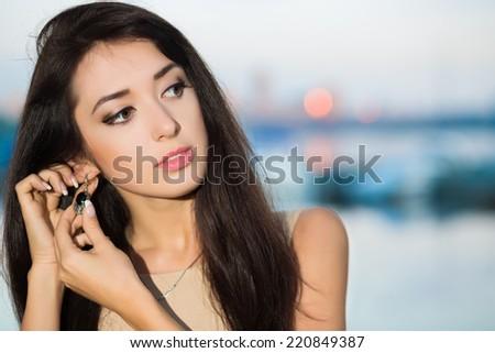 Portrait of pretty brunette wearing earring outdoors - stock photo